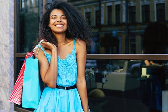 Close up photo of pretty African-American woman in a short turquoise dress, posing with shopping bags on her right shoulder, smiling and looking at the camera.