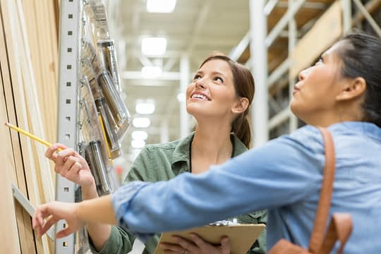 A cheerful mid adult female home improvement store employee stands with a clipboard and points to an item on a shelf.  She looks up as her customer studies the product.