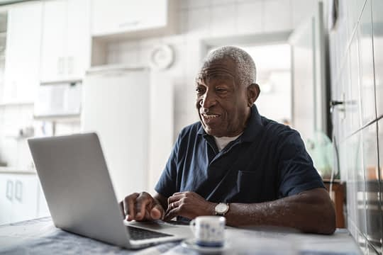 Senior man working at laptop at home