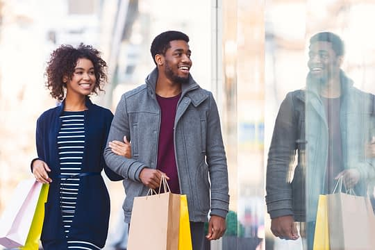Cheerful black lovers walking down the street with shopping bags in their hands, window shopping concept, free space